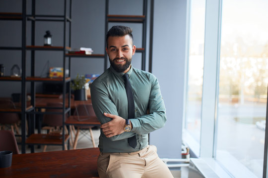 portrait of confident young handsome middle eastern businessman standing in office, looking at camera, successful team leader wearing formal wear, posing for photo at workplace