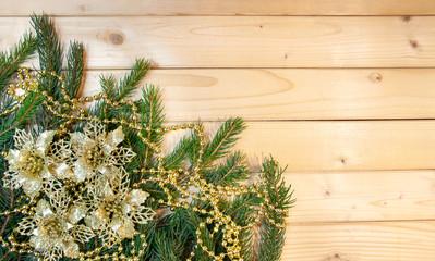 Fototapeta Bożonarodzeniowa dekoracja - gałązki świerku, złote kwiaty i złoty łańcuch na drewnianym tle obraz