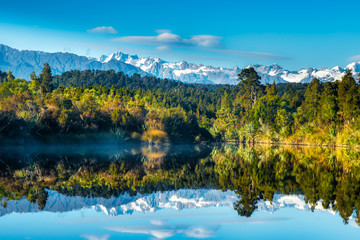 Mirror image reflections of the snow capped Southern Alps on Okarito Lagoon on the West Coast