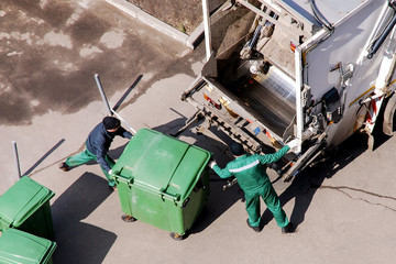 Garbage collection workers in residential area operating garbage truck, top view