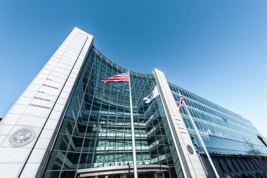 United States Securities and Exchange Commission SEC entrance architecture modern building sign, entrance, american flag, looking up sky, glass windows reflection in Washington DC