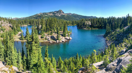 A high elevation volcanic mountain lake surrounded by hills and green trees.