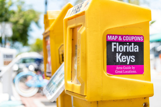 Key West, USA - May 1, 2018: Florida Keys newspaper, vending machine, kiosk, booth, box, dispenser with map, area guide, free coupons outside, outdoors, on street, by road