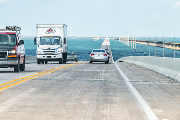 Piegon Key, USA - May 1, 2018: Point of view driving, moving in car on seven mile bridge landscape of Florida Keys water, atlantic ocean, cars on Overseas Highway US1 road, route