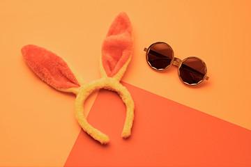 Fashion party girl neon Flat lay. Minimal. Woman Essentials night club accessories. Trendy sunglasses, rabbit. Coloful vibrant orange neon design Set. Creative pop art fashionable concept