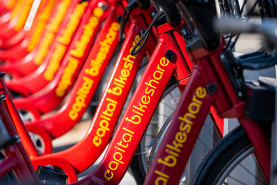 Washington DC, USA - April 5, 2018: Closeup of parked bike rent, rental parking at docking station near road from capital bikeshare red bicycles row on sidewalk street in capital city