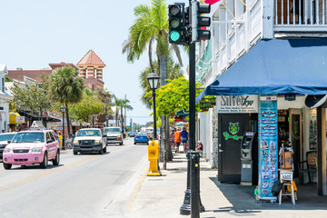 Key West, USA - May 1, 2018: Duval Street road, sidewalk in Florida keys city travel, sunny day on street, people tourists walking, cars driving, Silver kw jewelry store, shop