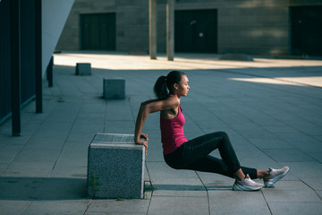Concentrated sporty woman outdoors exercising stock photo