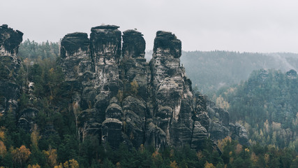 Rocky limestone mountain peaks scenery in autumn season. Moody foggy landscape at Bastei, Saxon Switzerland, Germany
