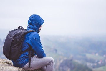 Lonely hiker wear outdoor clothing with backpack sitting on mountain edge, enjoying view of defocused valley. Travel adventure lifestyle harmony concept