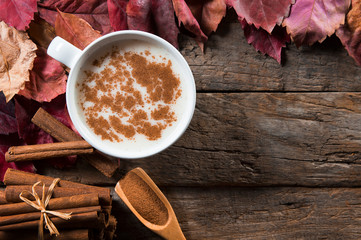 Top view white cup of salep milky hot drink of Turkey with cinnamon sticks, powder and autumn leaves on wooden backdrop Fototapete