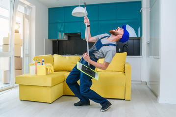Funny male cleaning worker in special blue clothes playing with a mop as a guitar like a rockstar in the stylish cuisine. Having fun at workplace.
