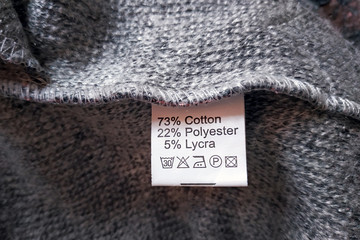 Wrong side of a gray dress made of wool, the composition is specified: cotton, polyester and lycra. Fabric composition clothes label on gray texture background. Fotomurales