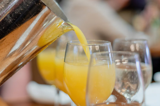Making mimosas - adding a splash or orange juice to the champagne