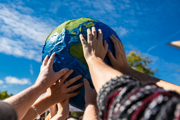 group of hands holding and protecting terrestrial globe as a symbol of environmentalism. Activist expresion of protest with cloudy blue sky