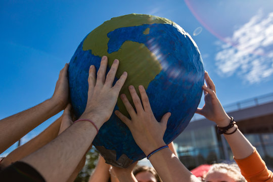 Close up of group of hands holding and protecting terra globe with lens flares. Activist expresion at protest in Saint Jerome
