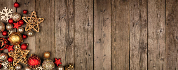 Poster Wood Red and gold Christmas ornament corner border banner. Above view on a rustic wood background.