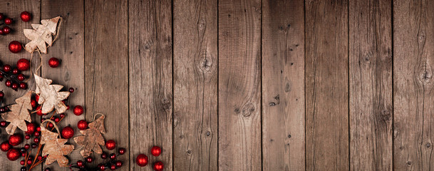 Wall Mural - Christmas corner border banner with wood tree decorations and red baubles. Top view on an rustic wood background.