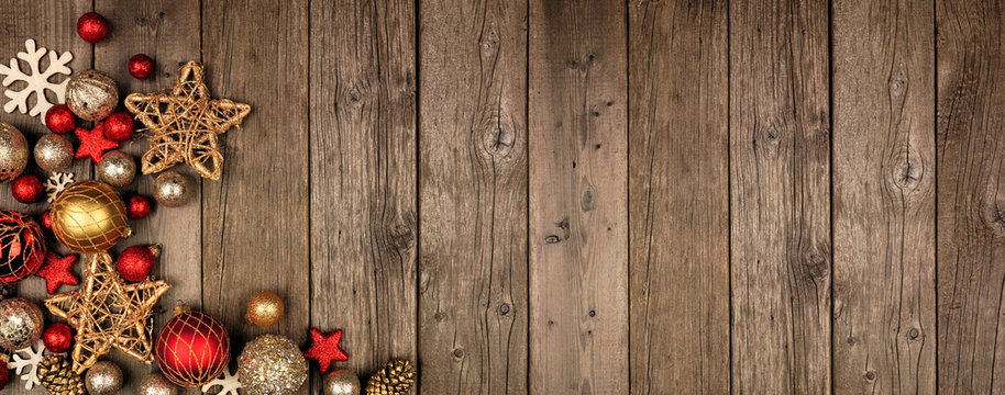 Red and gold Christmas ornament corner border banner. Above view on a rustic wood background.