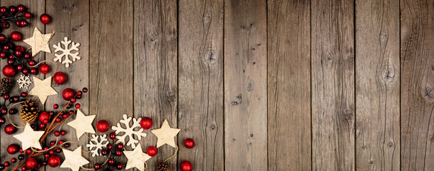 Christmas corner border banner with wood star ornaments and red baubles. Above view on an old wood...
