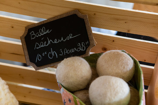 Close up of white dryer balls with its wooden and backboard hand writen sign with price and description. Green laundry product. Minerve farmers market