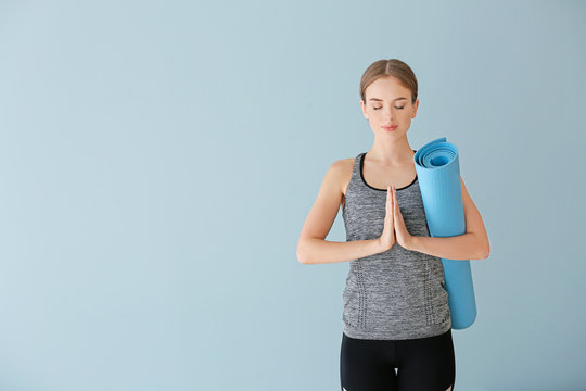 Young woman with yoga mat on color background