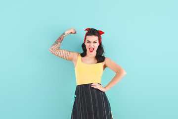 Portrait of strong tattooed pin-up woman on color background