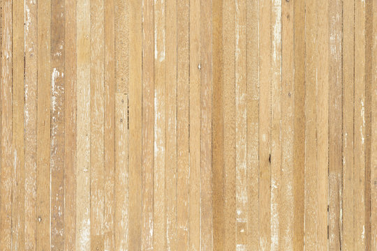 Wood texture background of old scratched wooden planks in light yellow beige color with some cracks.