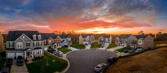 Aerial view of new construction street with luxury houses in cul-de-sac upper middle class neighborhood American real estate development in the USA with stunning red, yellow, orange sunset color sky
