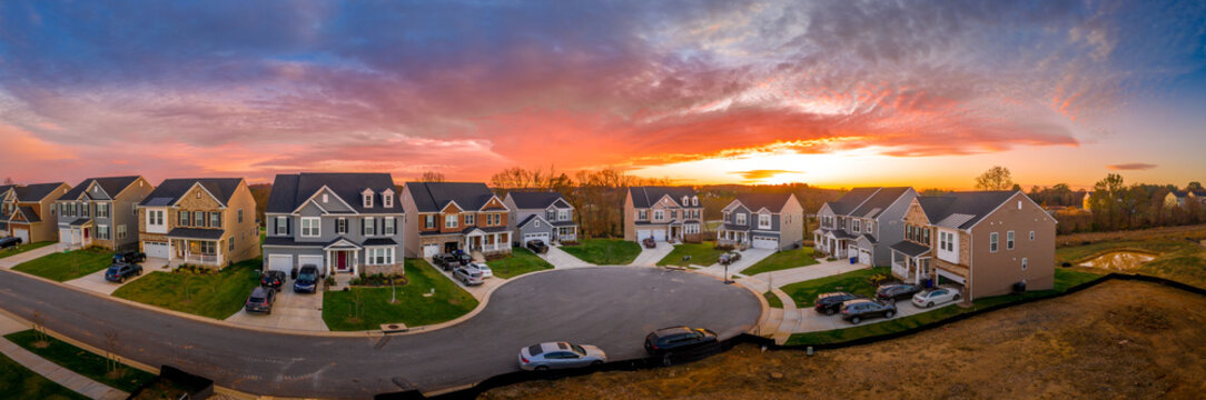 Aerial view of new construction cul-de-sac dead-end street with luxury houses in a Maryland upper middle class neighborhood American real estate development in the USA with stunning sunset orange sky
