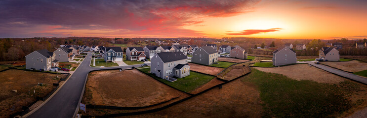Aerial sunset panorama of luxury real estate development single family house neighborhood street with dramatic sky in Maryland USA