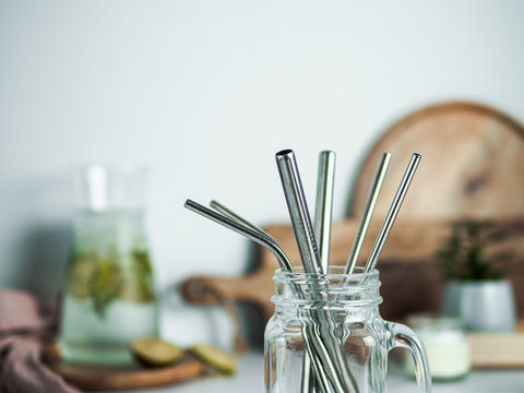 Metal drinking straws in glass mason jar indoor. Metal straws on table on kitchen table. Recyclable straws, zero waste concept.
