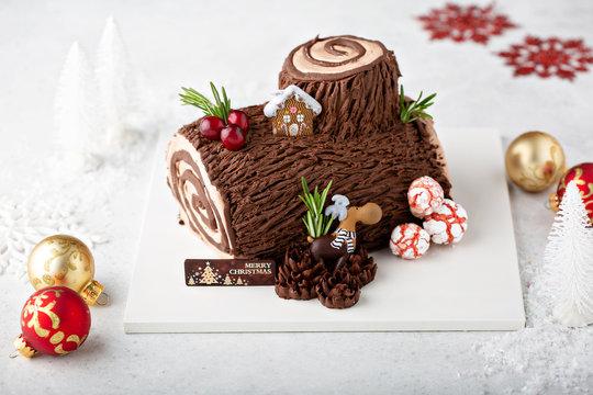 Christmas Yule log cake with edible sweet mushrooms and pine cones