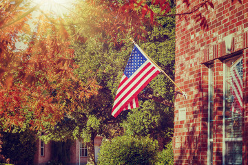 Patriotic American flag waving in front of a brick home on a sunny autumn day. Vintage filter effects.