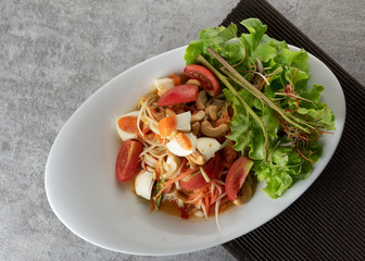 Papaya Salad with Salted Eggs on a plate , Somtum or Thai papaya salad