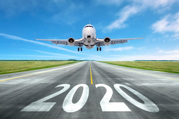 Poster Avion à Moteur The inscription on the runway 2020 surface of the airport runway with take off aircraft. Concept of travel in the new year, holidays.