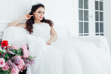 bride in a wedding dress and a crown sits in the white hall