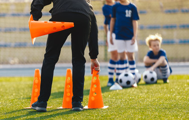 Soccer Coach Placing Training Cones for Kids Sports Team. Children on Soccer Football Class....