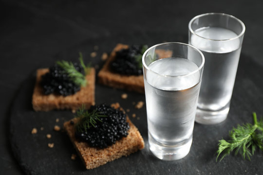 Cold Russian vodka and sandwiches with black caviar on table, closeup