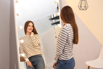 Beautiful young woman looking at herself in large mirror indoors