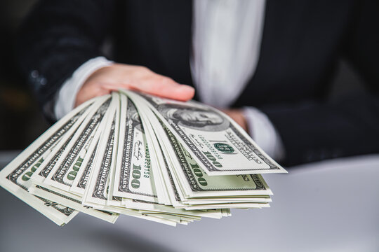 Rich Businessman giving and counting money, us dollars banknotes (USD) bills . Finance and Investing money. Currency broker with bundle of money. Making money with Business startup.