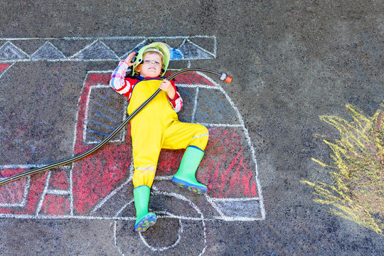 Little kid boy in fireman uniform having fun with fire truck picture drawing with colorful chalk on asphalt. From above. outdoors. Child dreaming of extinguish fire and future profession.