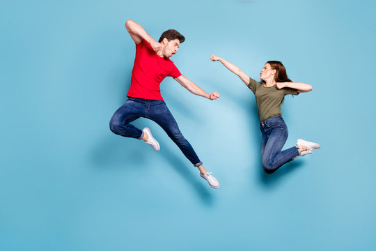 Full size photo of crazy man two people woman man spouses disagree jump fight kick boxing wear green red t-shirt denim jeans sneakers isolated over blue color background