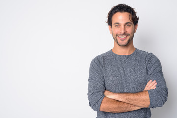 Portrait of happy handsome Hispanic man smiling with arms crossed Fotobehang