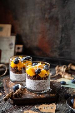healthy layered dessert white chia seeds pudding, chocolate granola, mango, blueberries