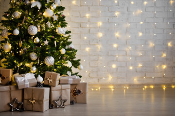 christmas tree and heap of gift boxes - copy space over white brick wall with lights