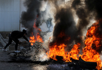 A demonstrator throws a tree branch on burning tires during ongoing anti-government protests in Tripoli