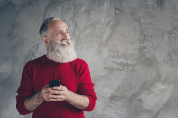 Profile side photo of dreamy positive white hair beard old man celebrate x-mas party work cellphone look copyspace think noel discounts wear trendy sweater isolated grey color background