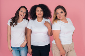 A group of girls in clean white t-shirts on a pink background. T-shirt mock-up for design on clothes