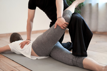 Brunette woman doing stretching on mat with male trainer